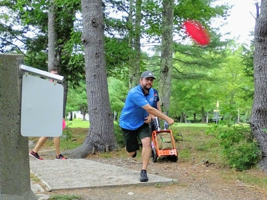 nate sexton throwing a roller off tee 16 of the eagle falcon course at sabattus disc golf
