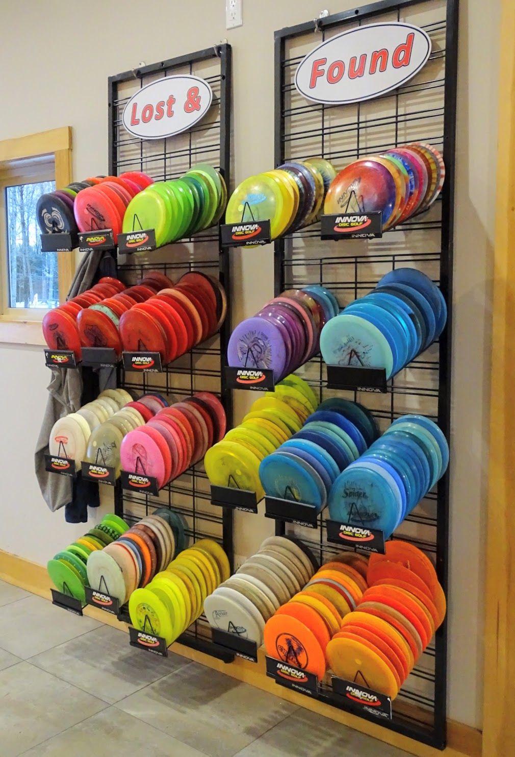 wall of lost and found discs at sabattus disc golf