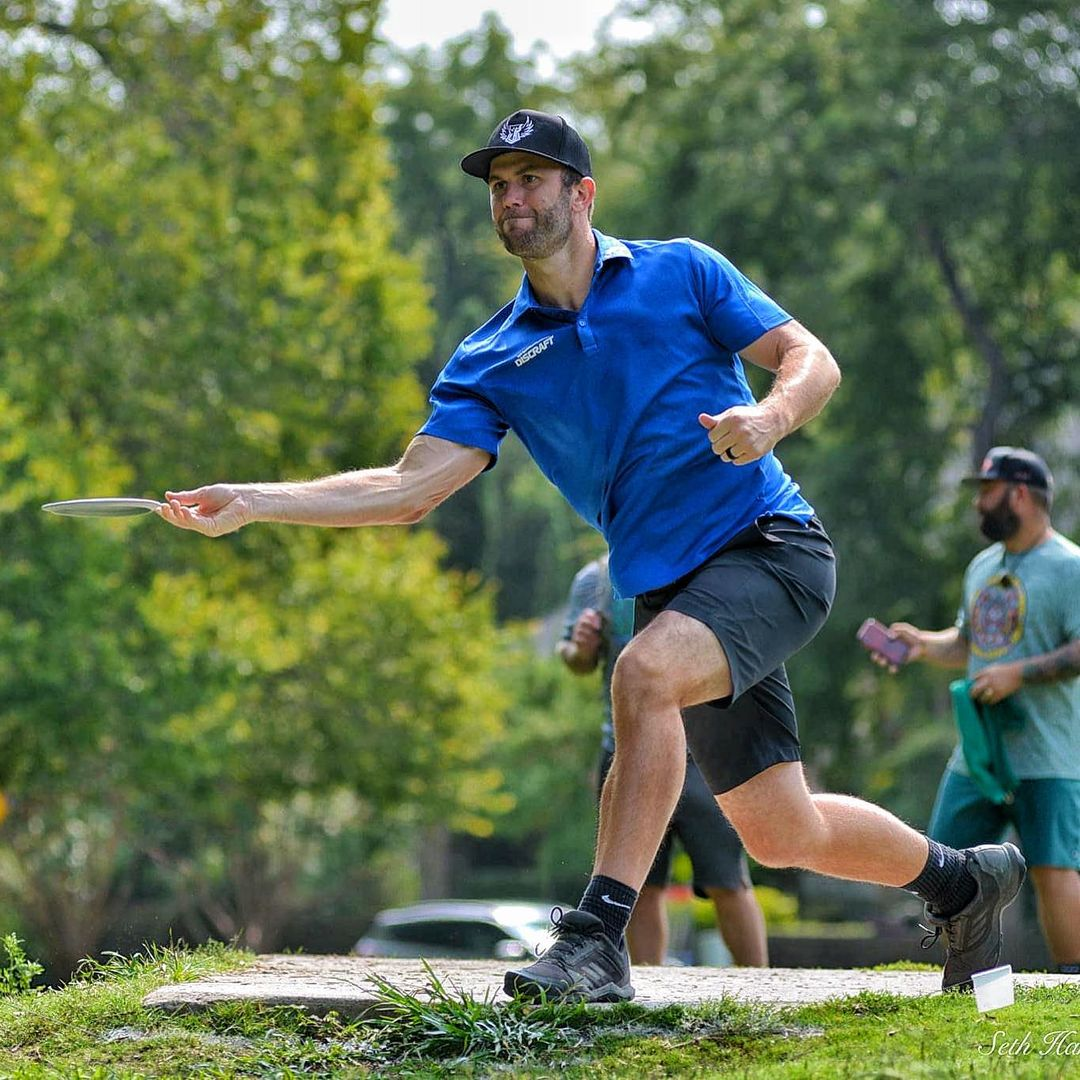 brodie smith throwing a forehand off a disc golf tee