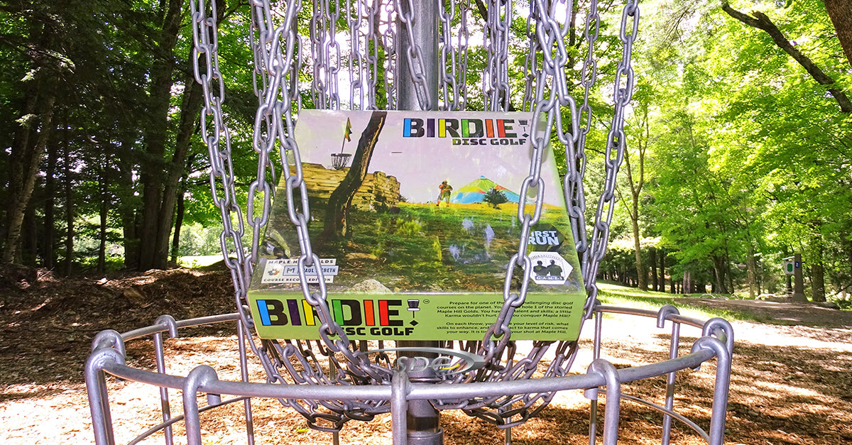 Birdie! board game hanging in the chains of a basket at sabattus disc golf