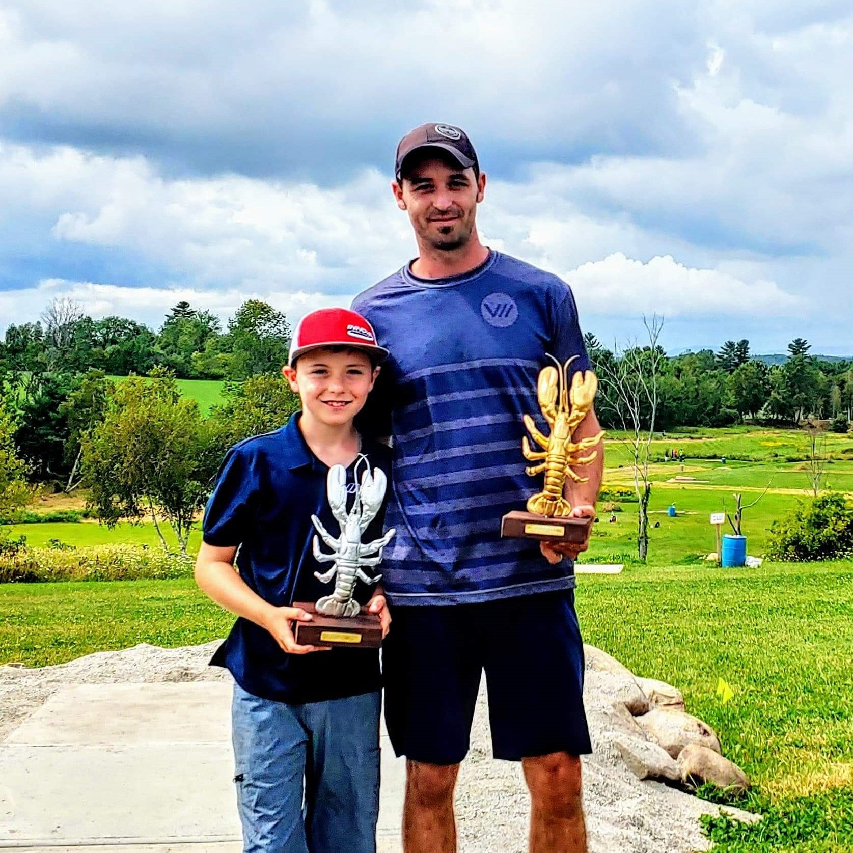 uriyah and kevin kelley with their lobster trophies at the maine state disc golf championship
