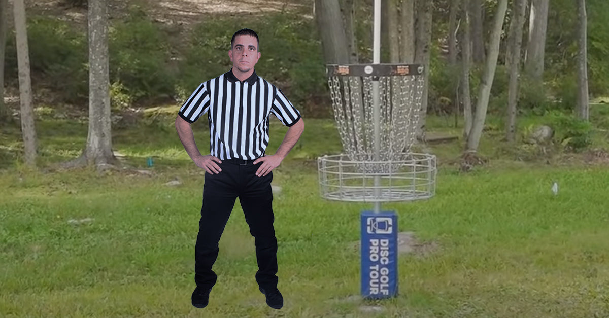 Black & white Striped Shirted Referee standing next to a disc golf basket