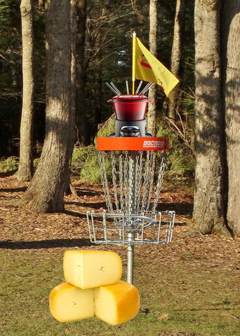 fondue pot on top of disc golf basket with wheel of cheese beside it for april fools day