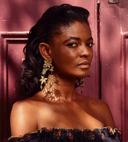 Portrait model posing in front of a red door, and glancing at the camera. They are wearing large, gold, mobile earrings, and an off the shoulder dress.