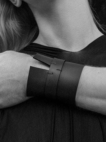 Person modeling black leather cuff jewelry worn on wrist, set in black and white.