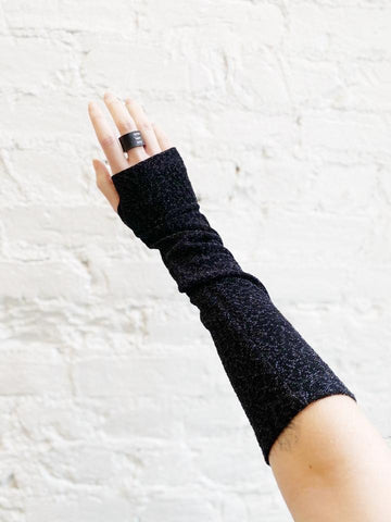 Pale hand against white brick background modeling a black, sparkly, fingerless glove, and a black leather ring.