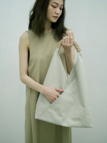 Person with long black hair pictured holding an ivory Kamaro'an bag against a neutral backdrop.