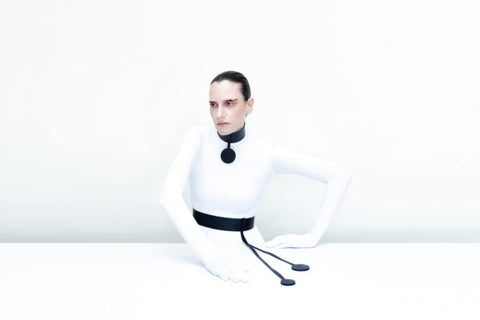 Model sitting and posing wearing a white top against a white background. Over the white top the model is wearing a leather choker and a leather waist belt.