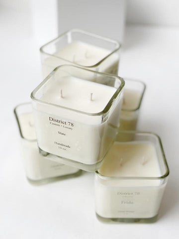 "Stack of white candles in clear, square, glass jars. In black ink the jars say ""District 78"""
