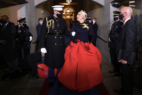 Lady Gaga is pictured linking arms with a US service member. She is wearing a red skirt, navy blue blouse, and white headpiece. Her blouse is adorned with a golden  brooch featuring a dove carrying an olive brand