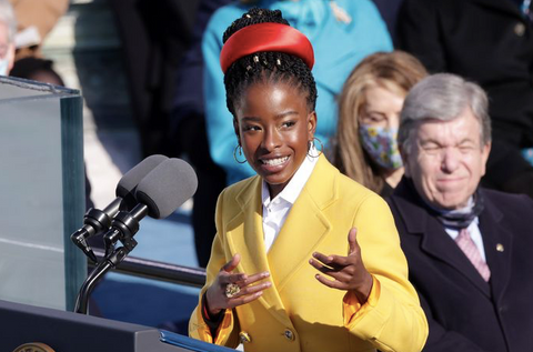 Black poet Amanda Gorman is pictured, gesturing to the crowd as she performs a poem. She is wearing a yellow Prada coat, and a bright red headband. Her hair is in braids and adorned with gold accessories.