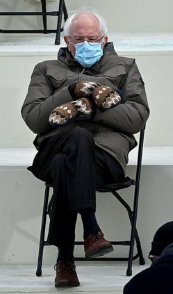 Senator Bernie Sanders is pictured sitting down wearing a blue surgical mask, a brown winter coat, and wool mittens. He is sitting in a metal folding chair, looking apathetic.