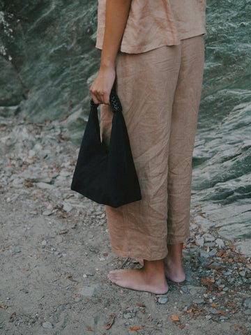 Photo of person from the hips down wearing a brown outfit, carrying a small black linen Kamaro'an bag.