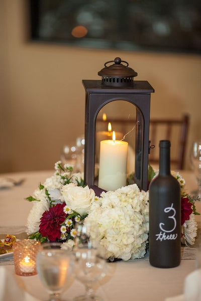 wedding centerpiece with lantern, flowers and chalkboard bottle