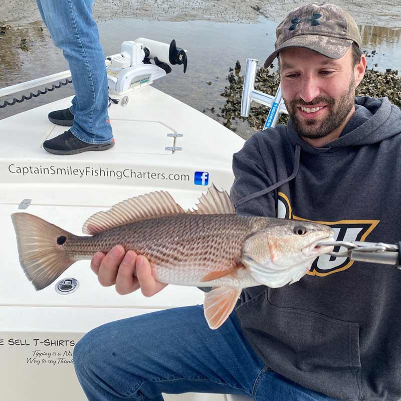 A nice low tide redfish caught with Captain Smiley Fishing Charters