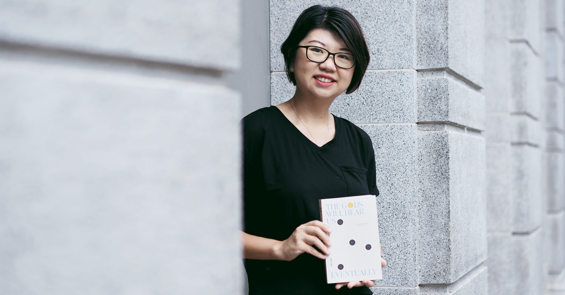 Author Jinny Koh holding a copy of her debut novel, The Gods Will Hear Us Eventually