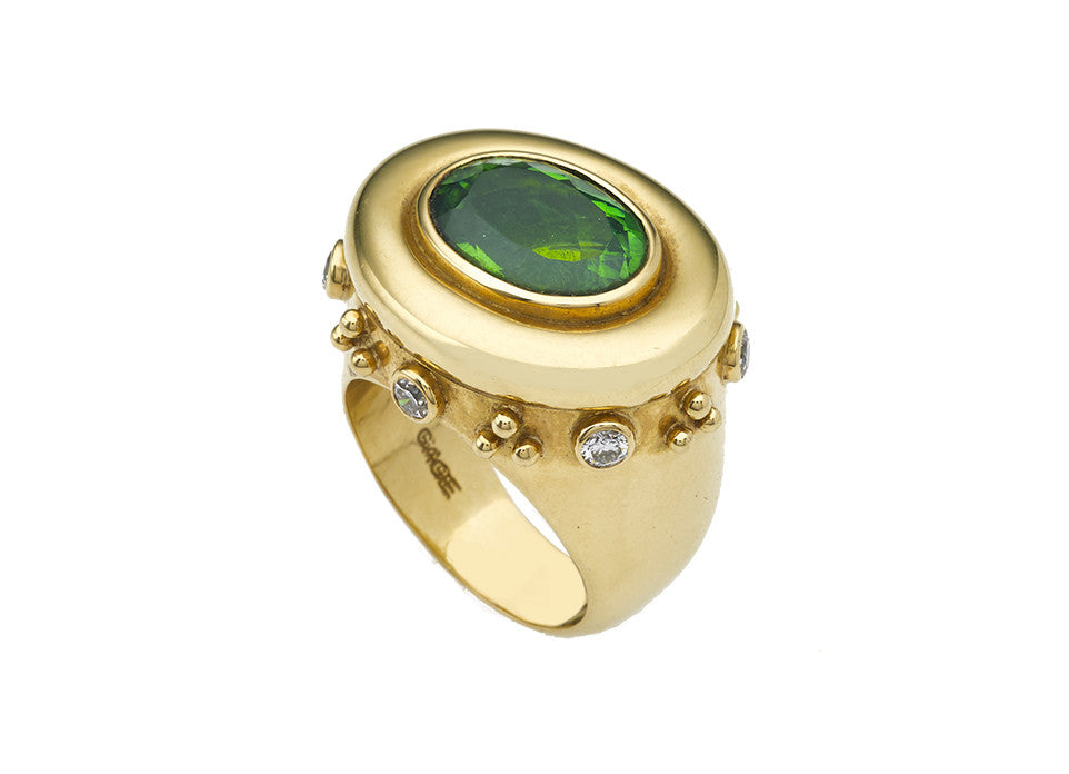Deep green tourmaline in a rounded surround on a gallery alternating with diamonds and trefoils of gold beads.
