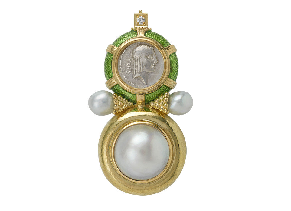 This striking Arcadia pin is set with a silver denarius coin with lime green enamel and gold wirework a round it. The lower part has a mabé pearl set in a lightly repoussé surround. On both sides of the pin are beaded funnels holding a grey pearl. At the top, a diamond is set in a square plinth decorated with beads.