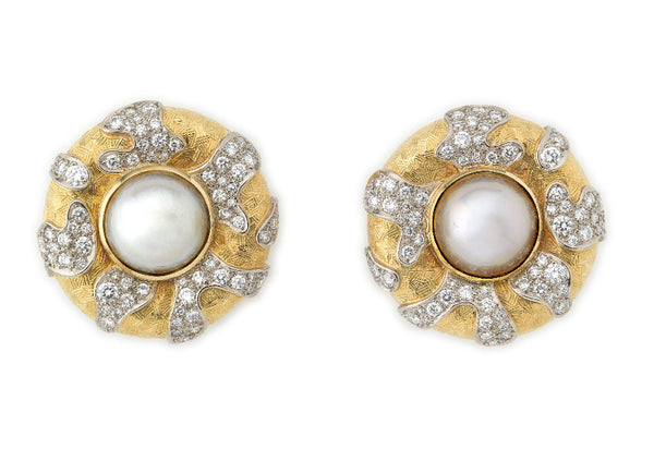 A stunning pair of round earrings set with mabé pearls in the centre of a yellow gold textured surround. Which is decorated with raised irregular shapes of white gold pave set with diamonds.