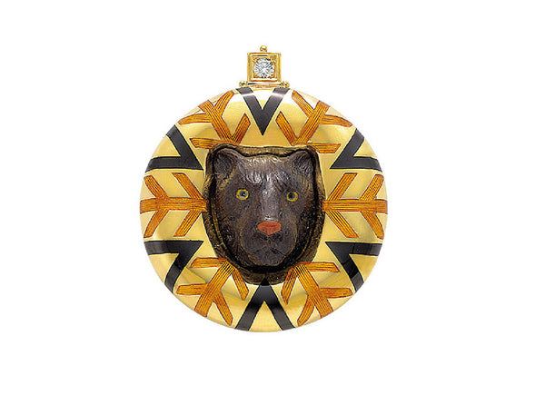 A fabulous pin featuring a carved petrified palm tree black panther head set in an 18ct yellow gold surround decorated with a striking orange and black enamel geometric design.  The pin is has a diamond set in the top square plinth with three gold beads around.