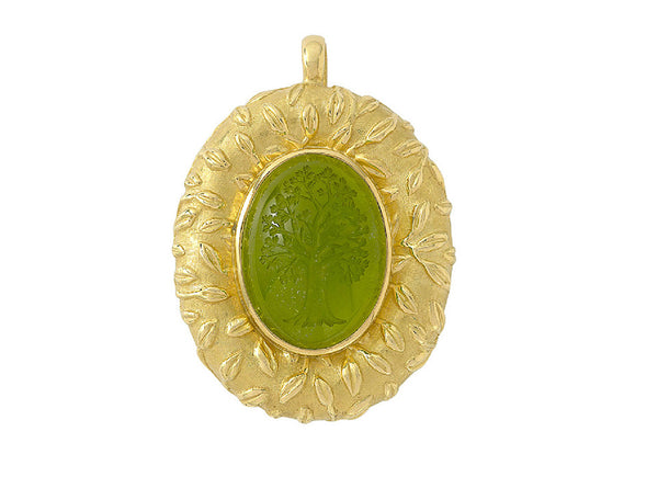A fabulous pendant featuring a beautiful oval peridot intaglio of a tree, set in a gold surround decorated with carved gold myrtle leaves.