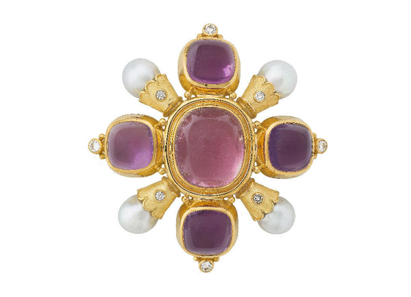 One of Elizabeth's beautiful Kiss Pins. In the centre is a cushion of pink tourmaline. On each of the four sides is set a square cushion of amethyst. At each corner is a south sea cultured pearl held in a scallop edged funnel with a diamond set on it. A diamond is set with bead detail on the outer edge of the amethyst settings.