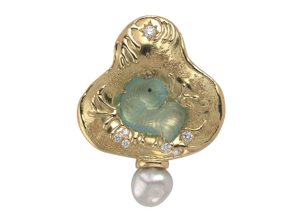 A wonderful 18ct yellow gold pin featuring a lovely aquamarine carving of a Kingfish wearing a gold crown with a pearl. Set in a gold surround decorated with granulation detail and a molten gold wave design.  In the surround at the top, in a star setting, is a diamond, more diamonds are set towards the base. The pin is finished with a baroque Keshi pearl to the bottom.