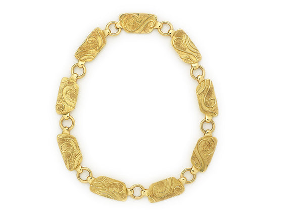 A fabulous 18ct yellow gold necklace comprising of nine plaques decorated with wire and granulation detail. The necklace is 16 inches in length.