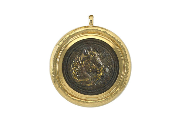 A gorgeous 18ct gold pendant featuring a Roman bronze horse head phalera (1st-3rd century AD) in a repoussé surround.