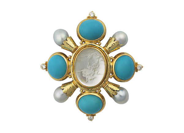 A stunning 18ct yellow gold Kiss pin featuring an oval rock crystal intaglio of a girl on a swing.  The centre has four oval cabochon turquoise in settings around it, alternating with lightly planished scalloped edge funnels holding a cultured pearl. On the outer edge of the turquoise settings is a collet set with a diamond and decorated with gold beads