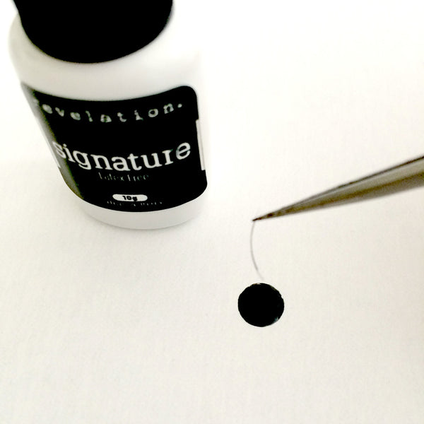 Image of Signature Latex Free Eyelash Extension Glue with tweezers coming into screen holing an individual eyelash extension being dipped in the glue.