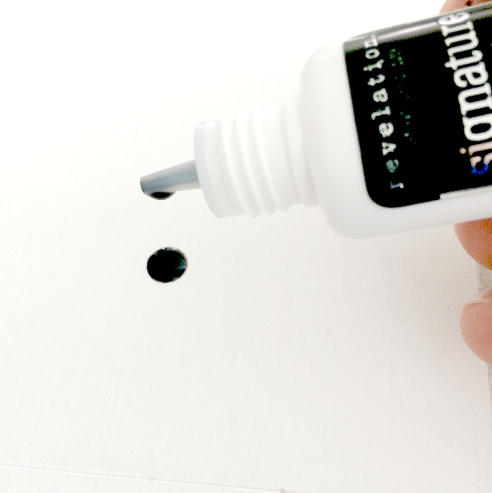Image of Signature Latex Free Eyelash Extension glue being poured out of bottle. Image shows a drop on white background.