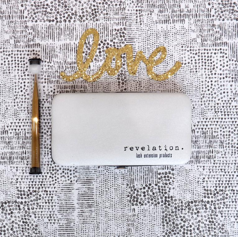 "Decorative magnetic lash case closed with gold tweezers beside it and the word ""love"" above in cursive."