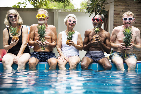 Adults dipping their feet at a pool with funny sunglasses and pineapples