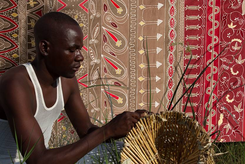 Weaving in front of a wall hanging