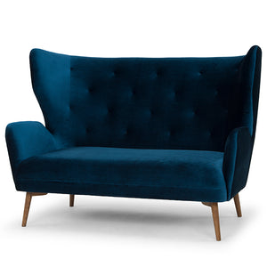 The Klara settee in midnight blue velvet with ash stained walnut legs