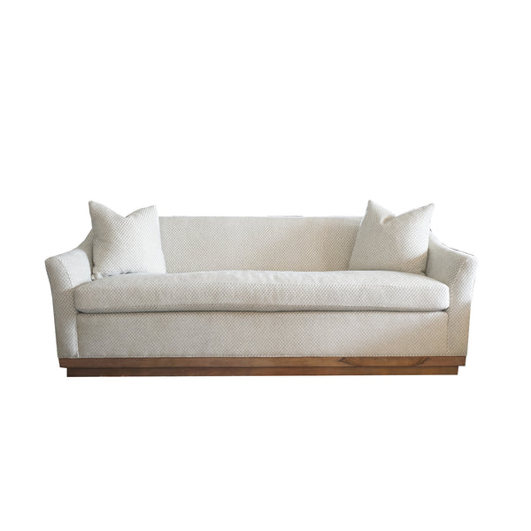 one cushion sofa in soft neutral green with wooden plinth base.