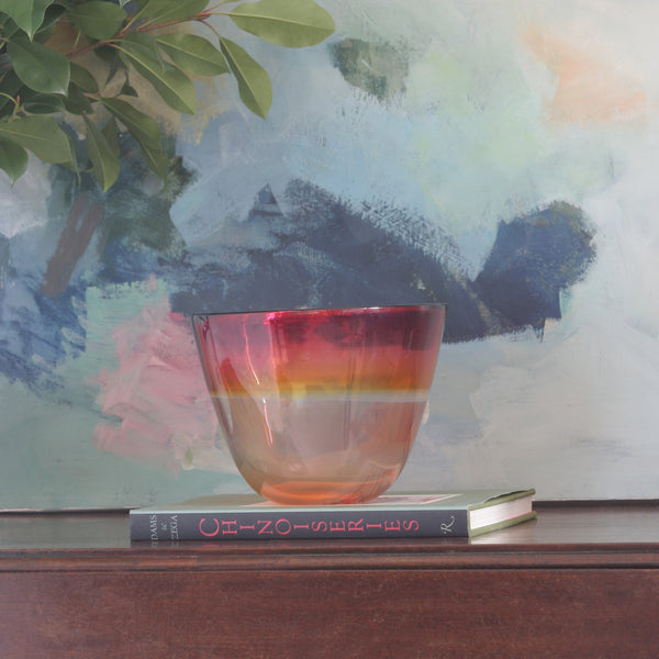 Mouth blown glass bowl in Red and Yellow in front of abstract painting