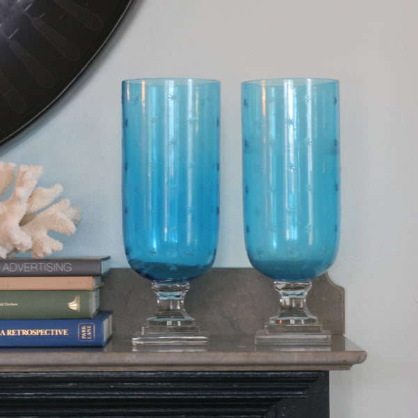 Pair of Blue glass hurricanes with etched star pattern on mantle