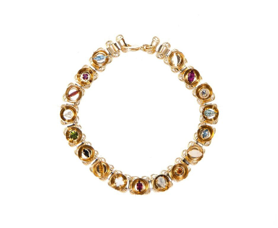 Colorful necklace in 14 kt plated gold with an array of different Swarovski crystals in different shapes inside concave spheres