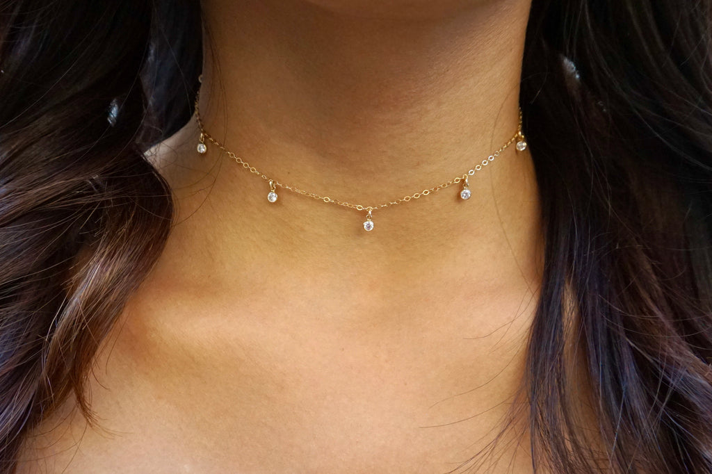 Seven-gem choker modeled on a woman with long hair.