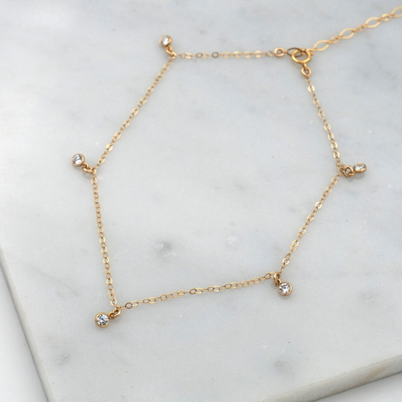 The 5-stone anklet.  Has a gold chain and five clear gemstones, with a dangling chain.