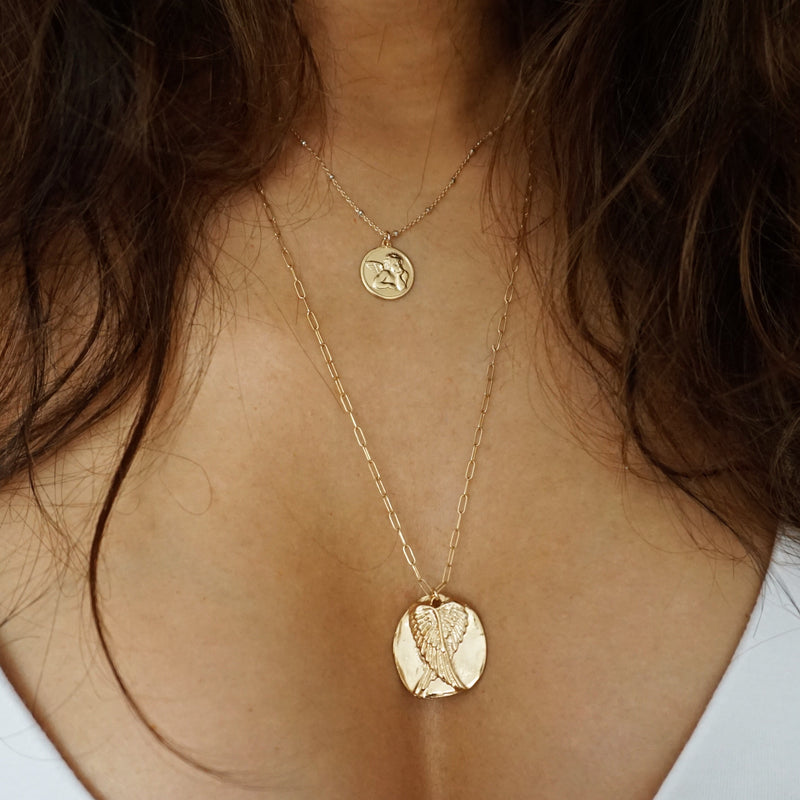 Comparison photo of the angel wings with the angel baby coin.  The wing coin is about twice as large and the chain is longer.