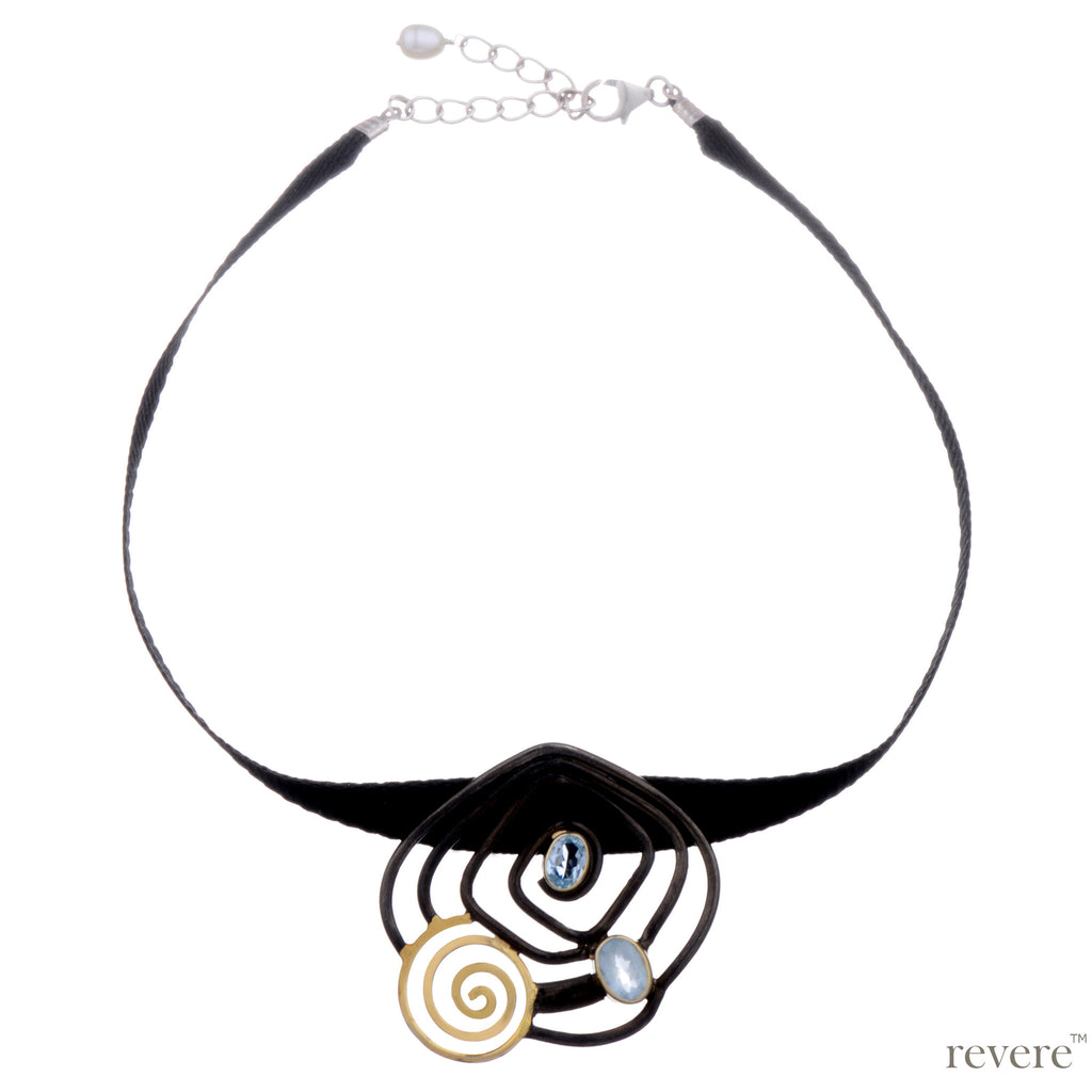 Neckpiece is a black ribbon choker with a hand made concentric oxidised and gold plated sterling silver pendant embellished with blue topaz ending with two inch sterling silver adjustable.
