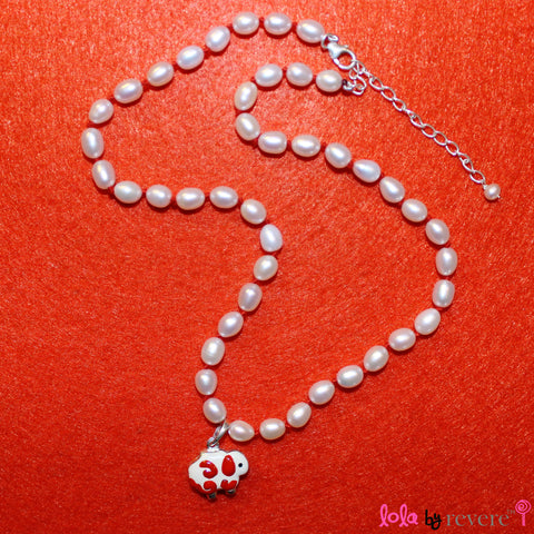 "White pearls handknotted in red thread to perfectly compliment the red and white sheep pendant in sterling silver. Measures 14"" with an adjustable chain of 2"" to increase length to 16"". Pretty and fun!"