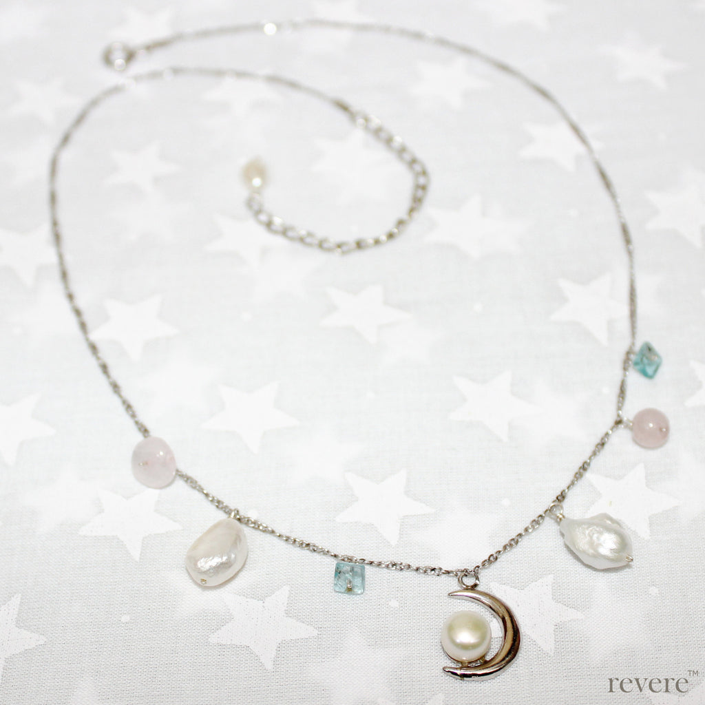 "A delicate crescent moon pendant crafted in pearl and sterling silver forms the center piece of the ""Moon & I"" necklace, suspended from a sterling silver chain with drops of keshi pearl and gemstones apatite and rose quartz. An accessory for anytime wear!"