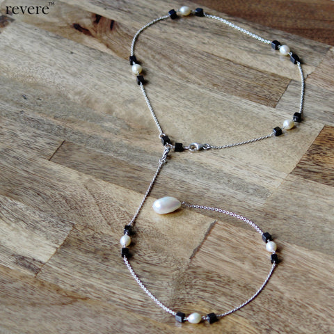 Featuring an elegant white freshwater baroque pearl suspended on sterling silver chain adorned with white freshwater pearl and black glass crystal.