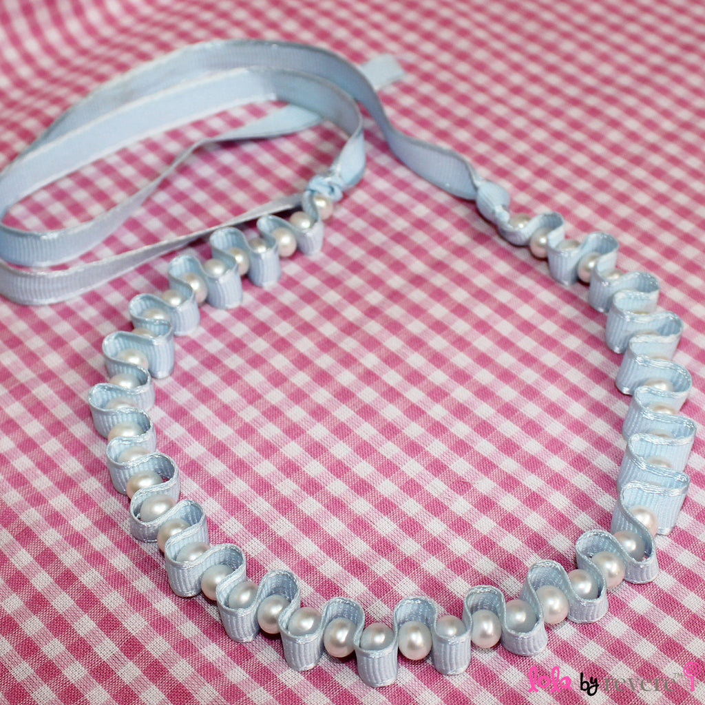 "Delicate freshwater water pearls woven into satin ribbon for a royal yet dainty effect. This piece measures 12"" around the neck and has 4"" ribbon tie on each side."