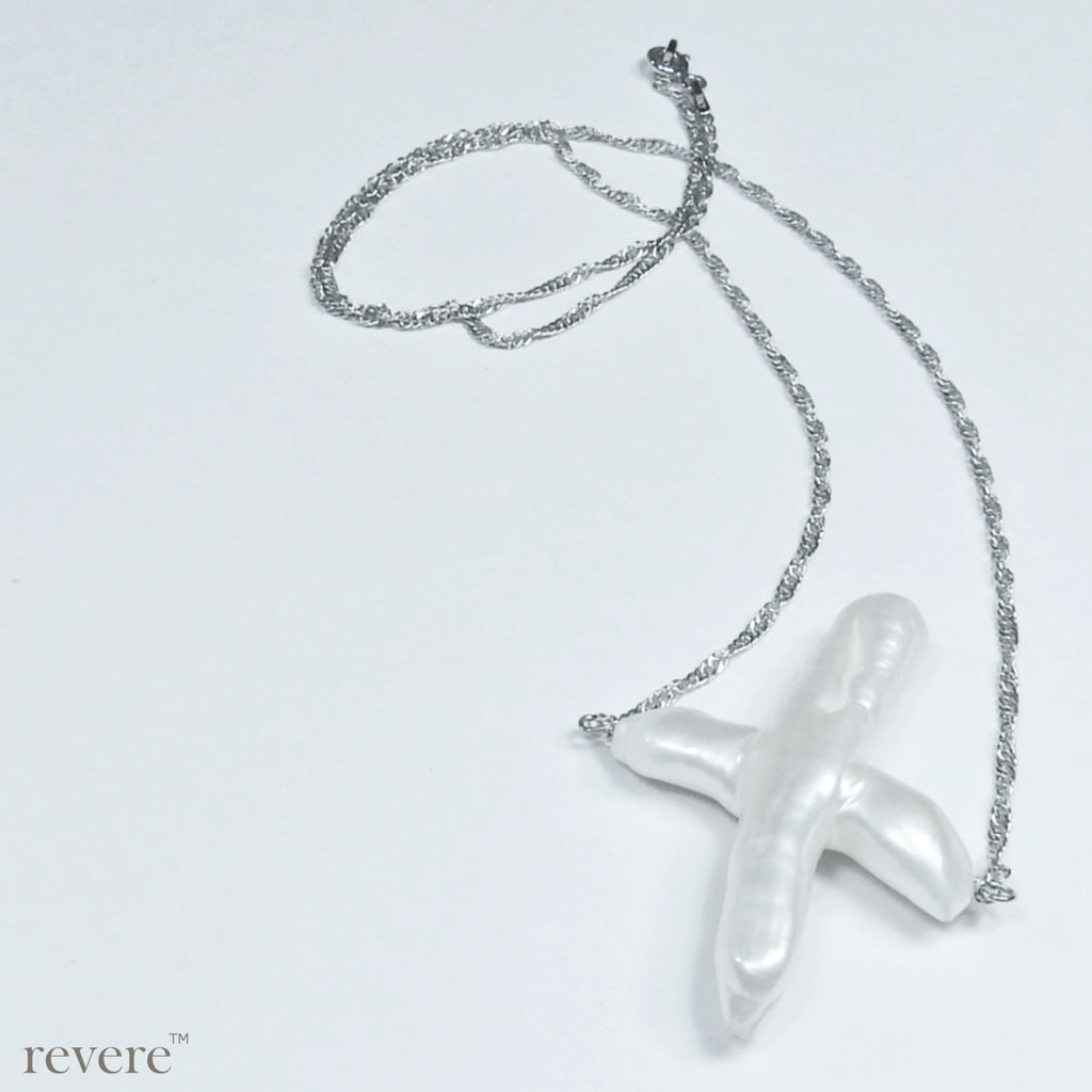 """Noel"" features freshwater white pearl, in the shape of a cross suspended on a delicate sterling silver chain with rhodium plating. A very unique shape for a pearl makes this a must have for your jewellery box!"