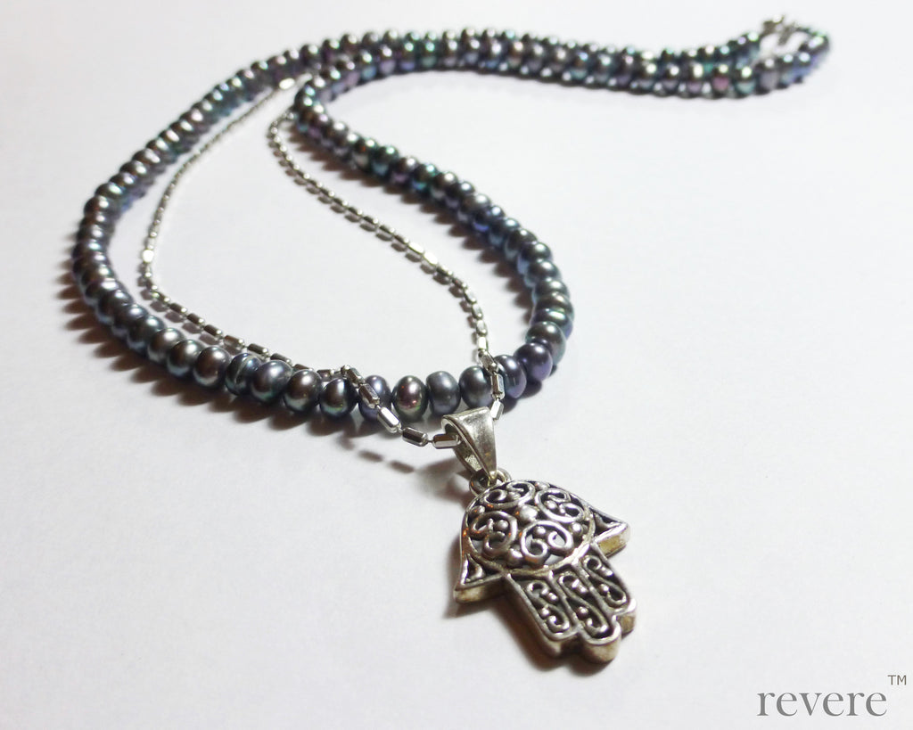 "This elegant strand of dark grey pearls is beautifully complimented by a sparkling silver chain and hand shaped charm pendant. ""Khamsa"" represents blessings, power and strength and is believed to be a sign of protection against the evil eye."